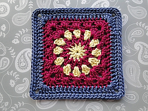 Cosmic Crochet Square with a yellow center, crimson middle, and dark blue edging.