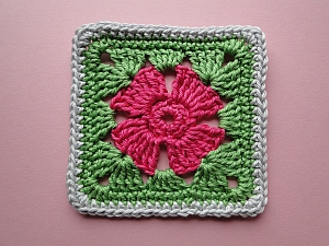 pink 4 petal flower surrounded by green and a plain grey edge