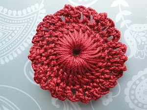 A deep red lacy edged circle, with a raised center