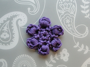 A small purple flower using a bullion stitch for each petal