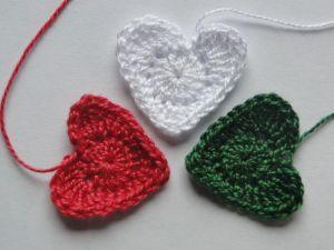 Three christmas hearts in red, white, and green