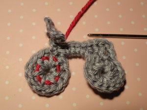 Crimson yarn woven under and over wheel stitches