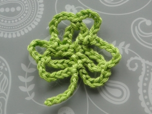 A green shamrock crocheted using chain stitch