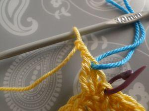 blue yarn through yellow worked crochet stitches