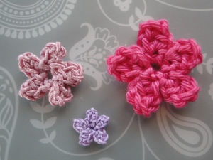 Three five petal flowers in different colors and yarns