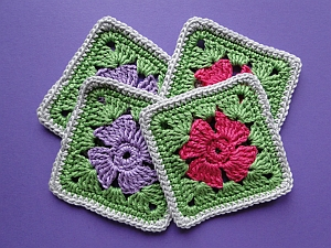Four crochet squares with flowers in the middle