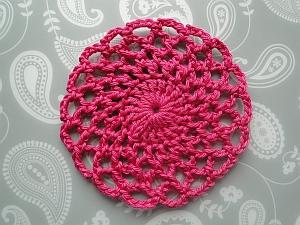 dark pink circular lacy crochet coaster