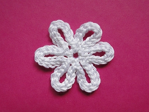 A white slip stitched crochet flower with six petals