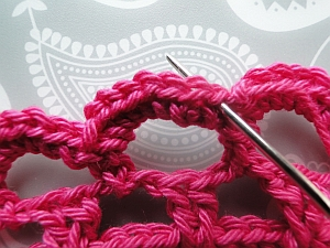 Needle going under top two loops of same stitch to weave in end
