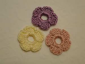 Three five petal flowers in purple, pink and yellow