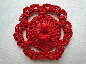 Dark red flower with two sets of loops around a circle forming the petals
