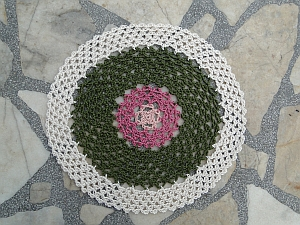 Doily in four colors: light and dark pink, green, and a cream edging.