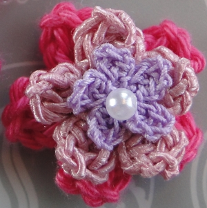 A three layer flower with a pearly bead in the center