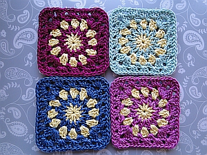 The four coasters shown in magenta, green, blue and pink, each combined with a yellow sun pattern.
