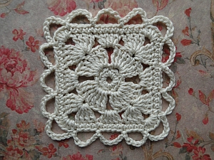 Chain loop edging around a white crochet flower square