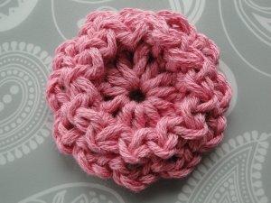 Dark pink flower in worsted yarn. Width: 1 ¾