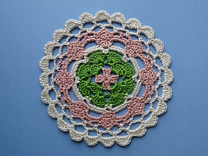 Coaster worked in pink, green, and cream