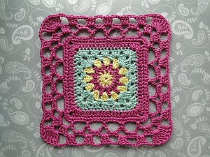 A green, pink and yellow square, surrounded by lacy pink work