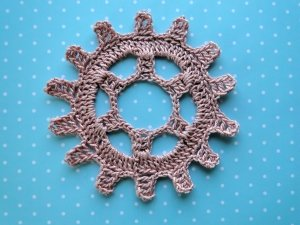 Pink steampunk gear wheel crocheted in size 10 thread.