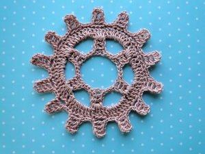 Pink steampunk gear wheel crocheted in size 10 thread.