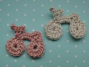 A pink and a gray crocheted bike